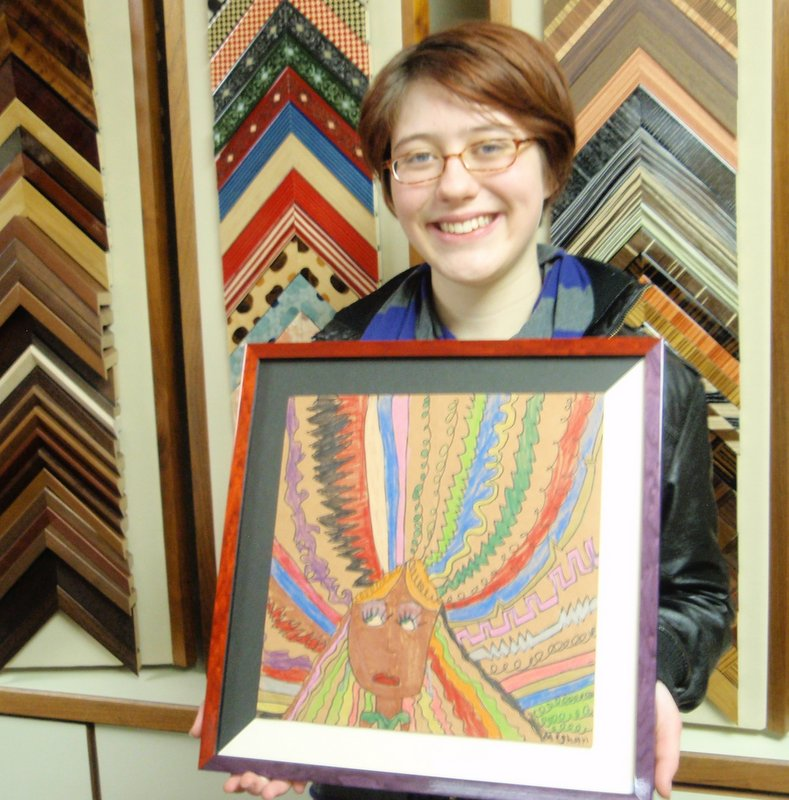 Meghan and her newly framed artwork                               from youth